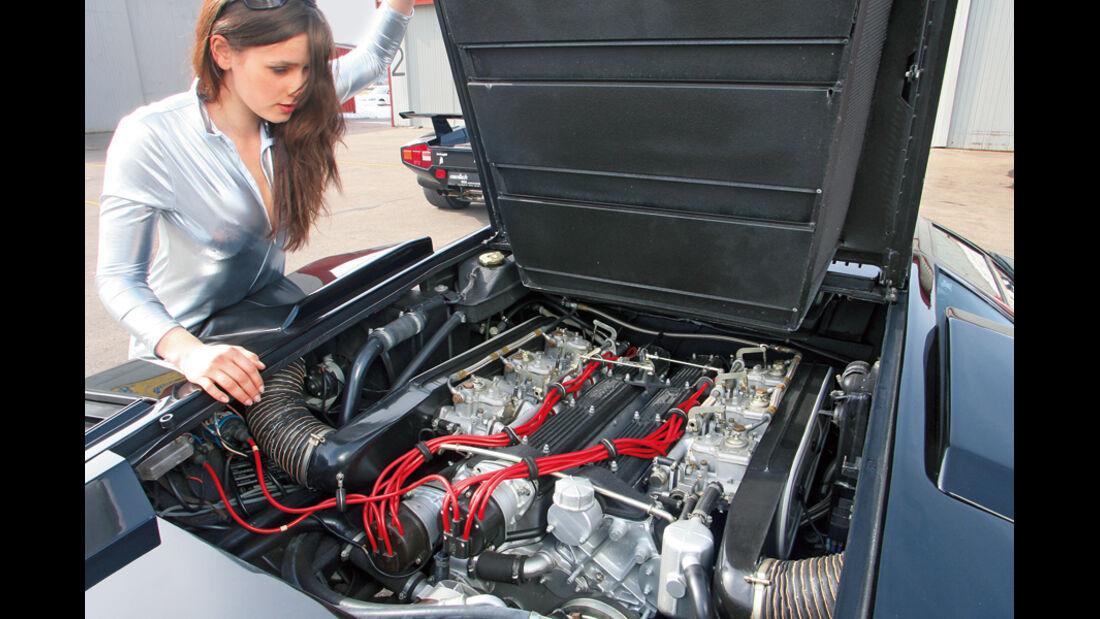 Brünette im silbernen Catsuit blickt auf den V12-Motor des Lamborghini Countach LP 400