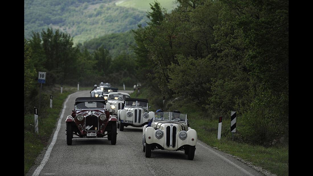Drei weiße BMW 328 überholen roten Alfa Romeo auf der Mille Miglia