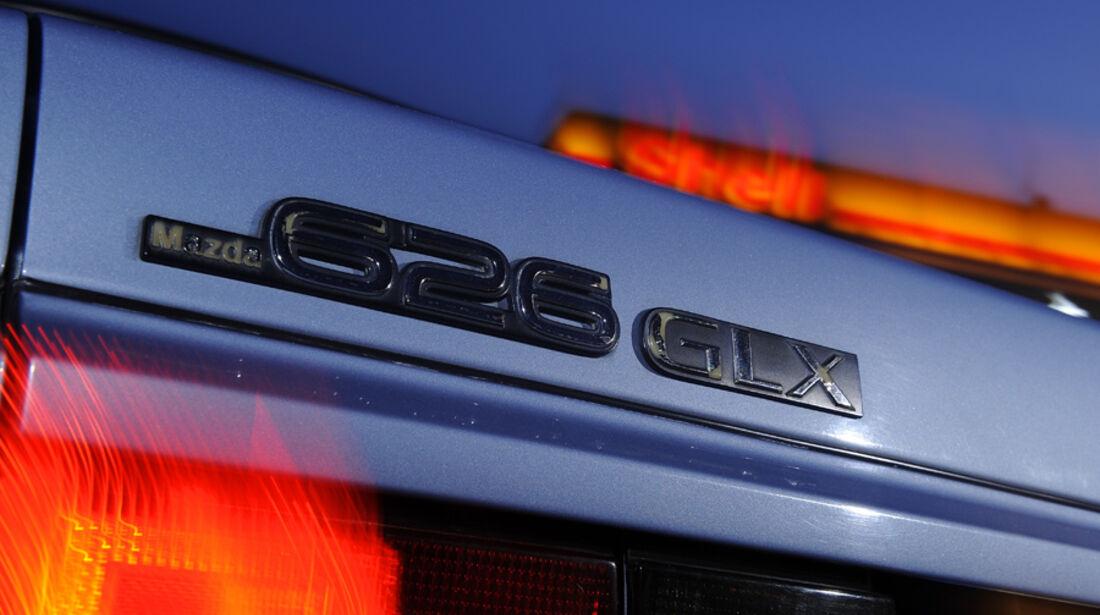 Emblem und Typenbezeichnung am Heck des Mazda 626 Coupé 2.0 GLX, Baujahr 1983