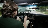 Fahrer hinter dem Steuer eines orangenen Pontiac GTO