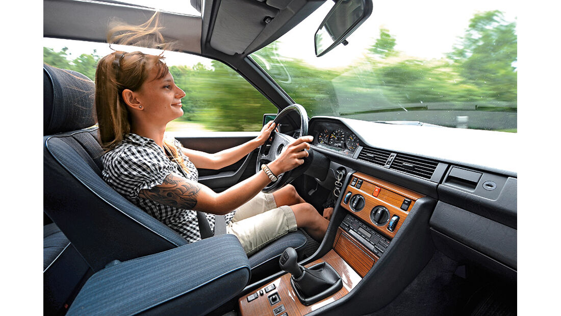 Frau am Steuer eines Mercedes 300 CE