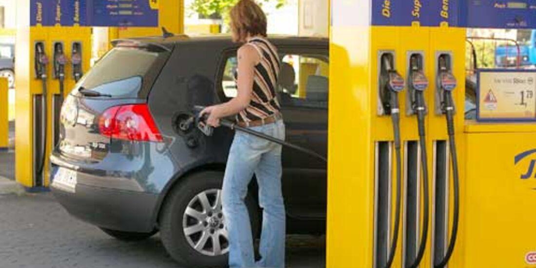 Frau an Tankstelle