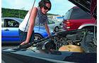 Frau blickt auf VW Golf 1 Motorraum