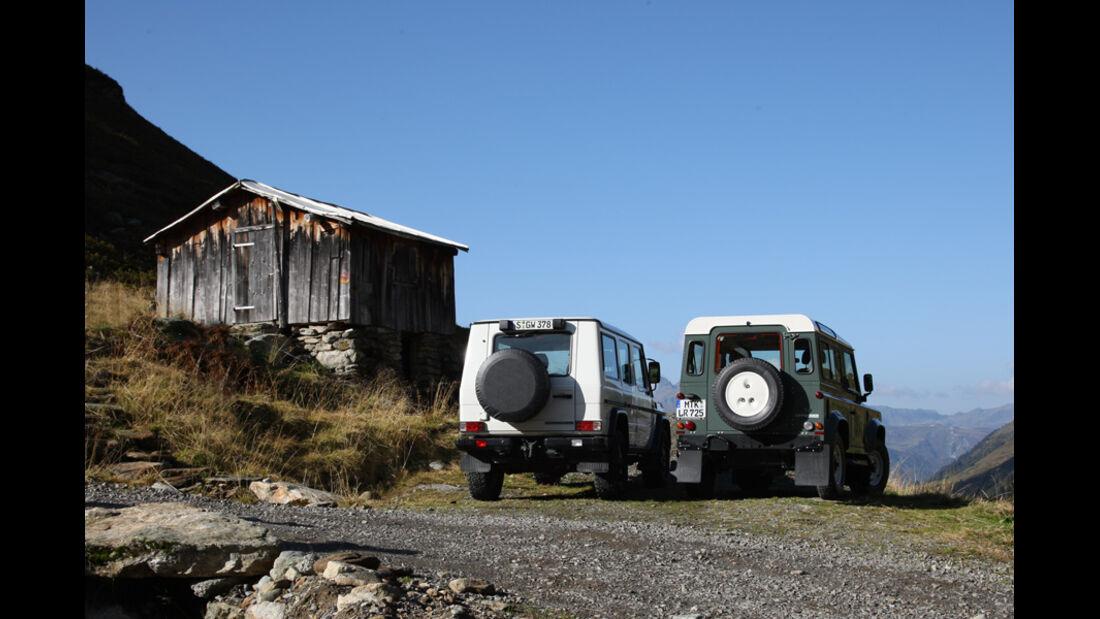 Land Rover Defender 90 TD4, Mercedes-Benz G 280 CDI Edition Pur - Heckansicht vor Berghütte