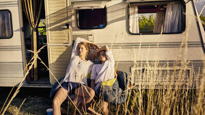Mother with daughter relaxing at a caravan