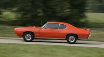 Orangener Pontiac GTO in Fahrt Seitenansicht