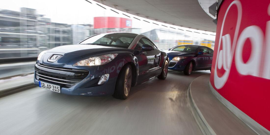 Peugeot RCZ und Renault Mégane Coupé im Parkhaus