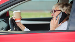 Reckless, smiling mature woman talking on the phone and holding a cup of coffee while driving a car