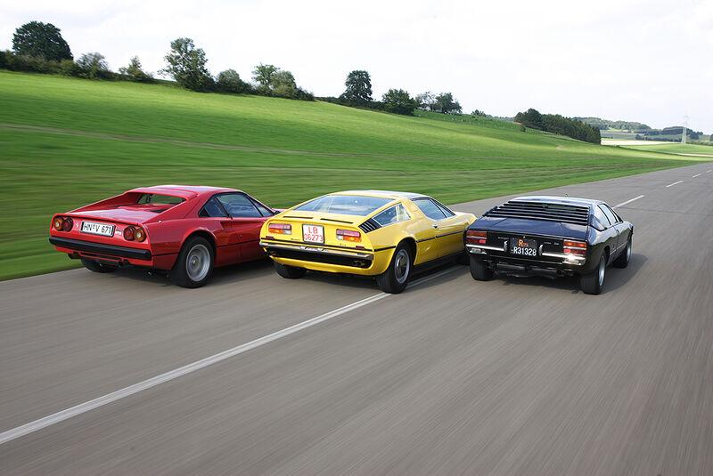 Roter Ferrari 308 GTB, gelber Maserati Bora 4.7 und schwarzer Lamborghini Urraco P 300 in Fahrt von hinten