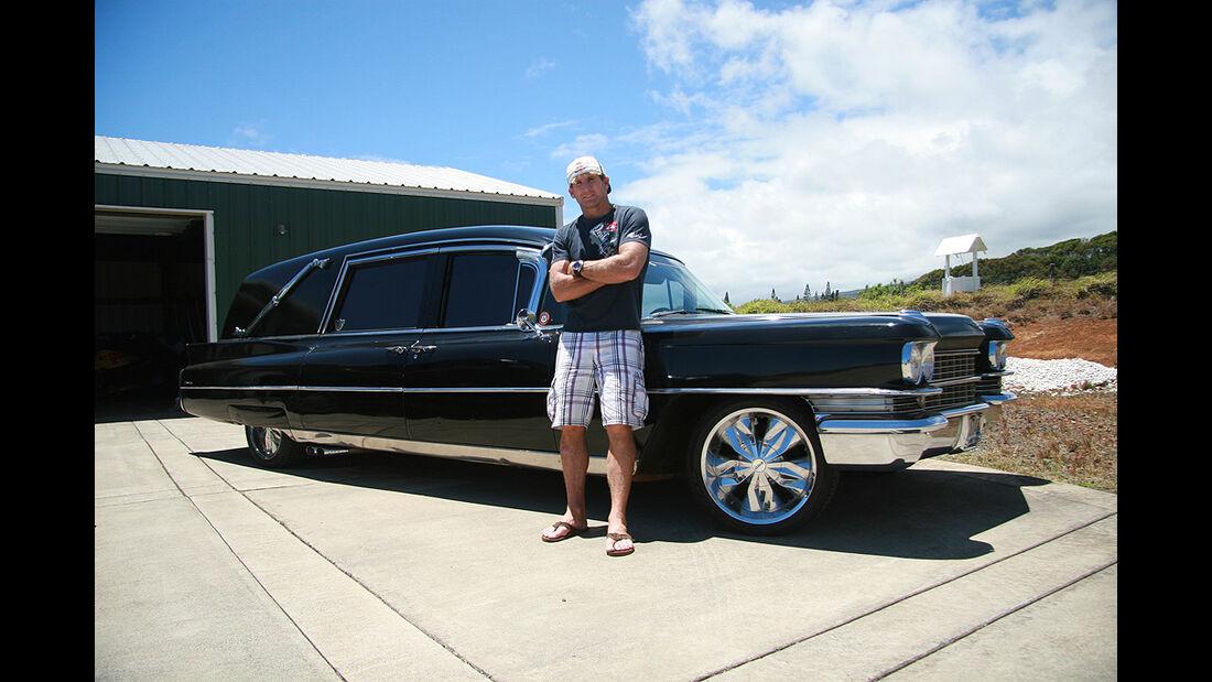 Surfer Robby Naish vor seinem umgebauten Cadillac-Leichenwagen