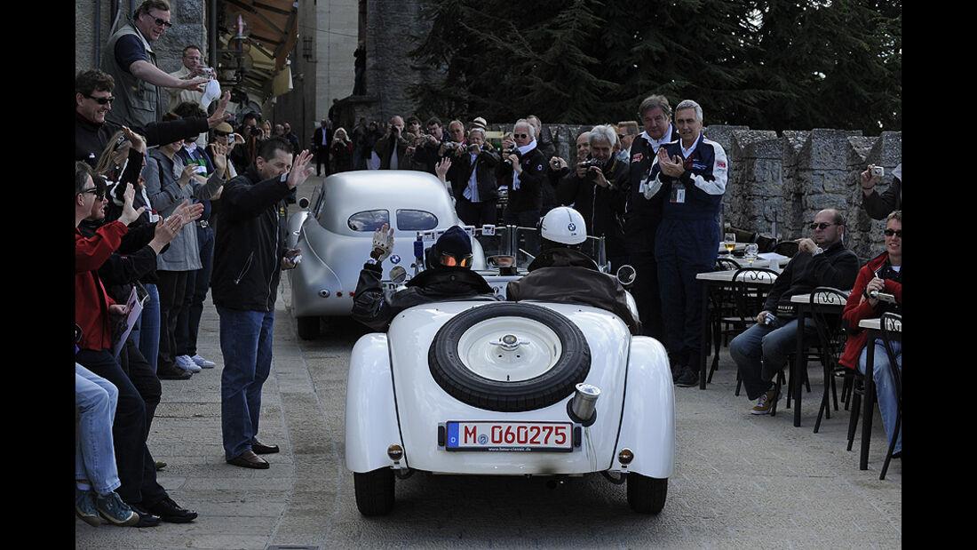 Zwei BMW 328 fahren durch Menschenmenge